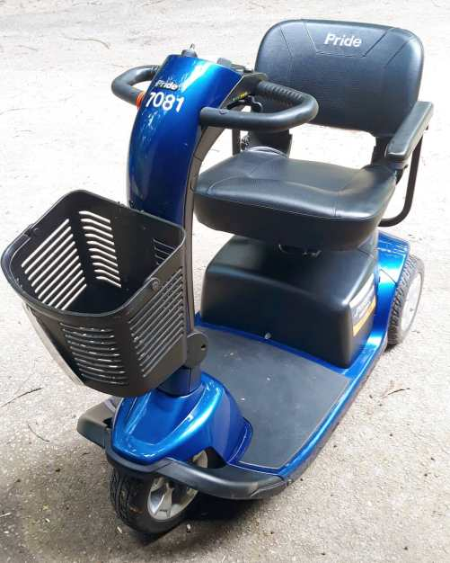 Pictured: A blue and black motorized 3 wheel mobility scooter with a black basket attached to the front. The words Pride appear in white along the front of the seat back.