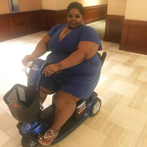 A plus size brown African American woman with short cut curly hair, slight smirk on her face, wearing a deep V royal blue short romper set, seated on a blue mobility scooter with black basket attached to the front.