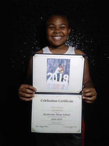 "A young African American boy, medium brown complexion, standing in front of a black sparkly backdrop, holding an elmentary school diploma that reads ""Celebration Certificate 2019"". The boy is grinning."